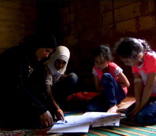 Syrian Refugee woman helps her daughters with homework